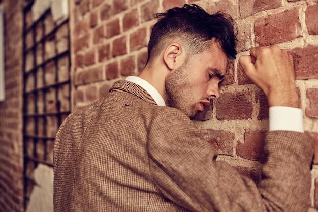 Jonge man slaat zijn vuist op de bakstenen muur. hij heeft een probleem