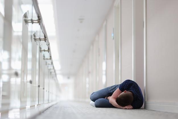 Jonge man slapen onder gesloten deur van hotelkamer hotel
