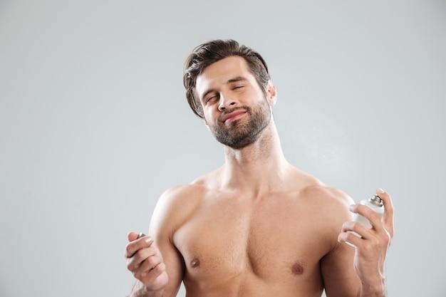 Jonge man sluitende ogen tijdens het gebruik van parfum