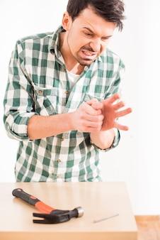 Jonge man sneed zijn vinger, terwijl hamer een spijker.