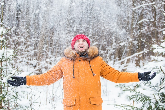 Jonge man sneeuw gooien in winter forest. kerel die buiten plezier heeft. winteractiviteiten.