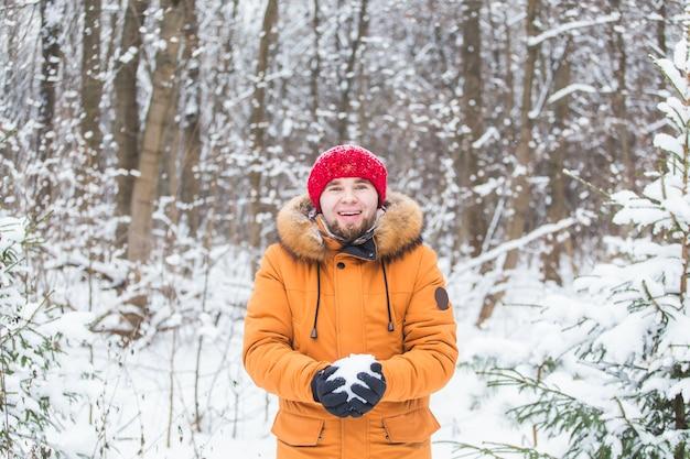 Jonge man sneeuw gooien in winter woud. guy plezier buitenshuis. winteractiviteiten.
