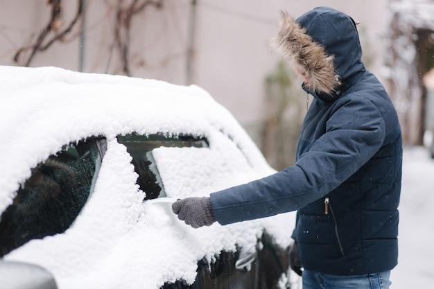 Jonge man sneeuw uit de voorruit van de auto buiten in de buurt van de garage op winterdag schoonmaken