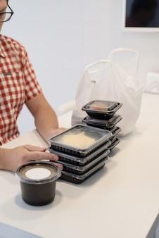 Jonge man sorteert voedselbezorgdozen in de keuken