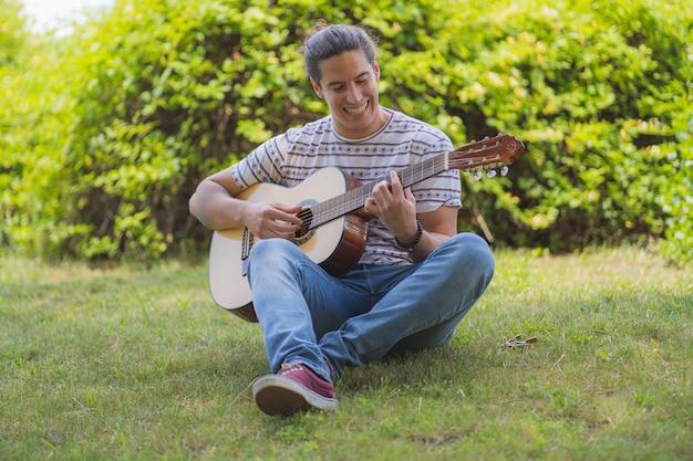 Jonge man spaanse gitaar spelen lachend op het veld