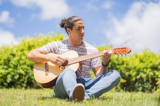Jonge man spaanse gitaar spelen op het veld