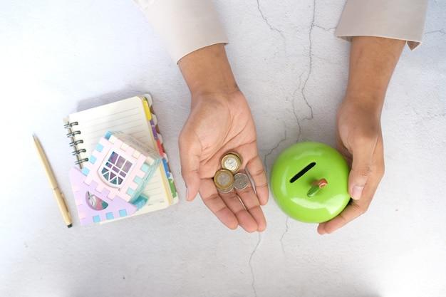 Jonge man spaart munten in een pot en schrijft op notitieblok