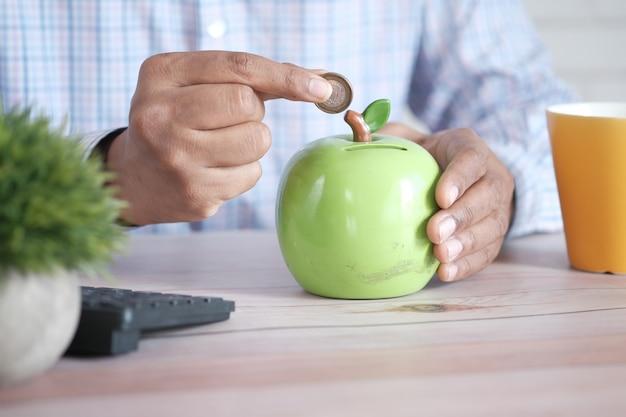 Jonge man spaart munten in een witte pot