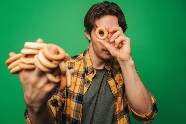 Jonge man speelt cookie en bedekt, geïsoleerd op groene achtergrond.