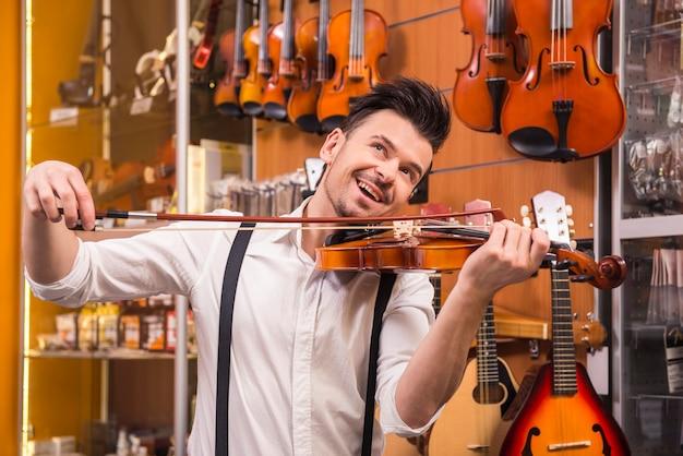 Jonge man speelt een viool in een muziekwinkel.