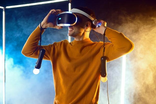 Jonge man speelt het spel met behulp van virtual reality headset en gamepad in lichtgevende kubus