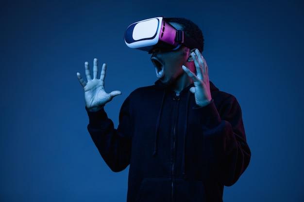 Jonge man speelt in vr-bril in neonlicht