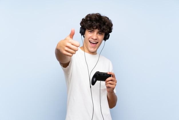 Jonge man speelt met een videogamecontrolemechanisme over geïsoleerde blauwe muur met omhoog duimen omdat er iets goeds is gebeurd