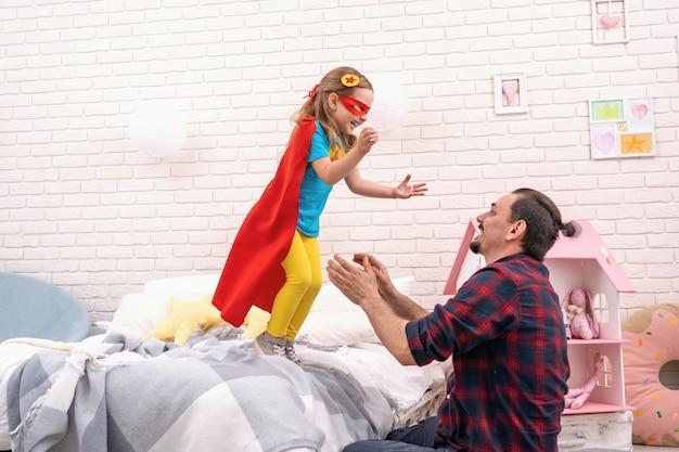 Jonge man speelt met zijn dochter in superhelden in de kamer.