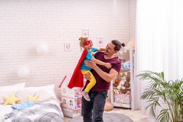 Jonge man speelt met zijn dochter in superhelden in de kamer