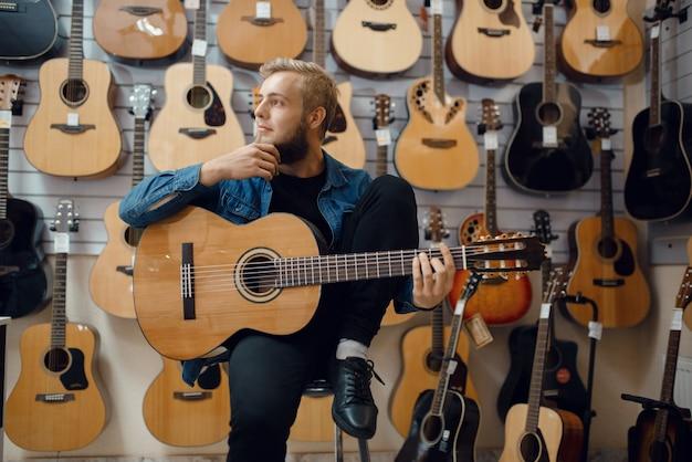 Jonge man speelt op akoestische gitaar in muziekwinkel. assortiment in muziekinstrumentenwinkel, mannelijke musicus die apparatuur koopt