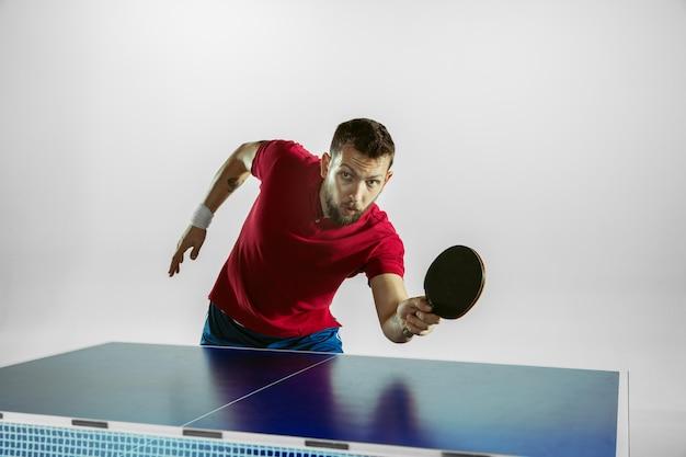 Jonge man speelt pingpong op witte muur.