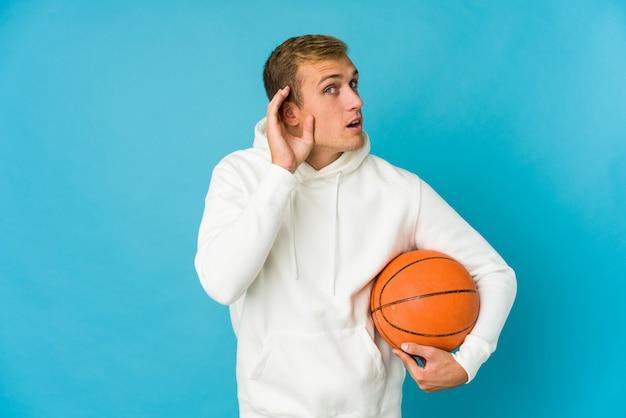 Jonge man spelen basketbal geïsoleerd op blauwe muur persoon met de hand wijzend naar een shirt kopie ruimte, trots en zelfverzekerd