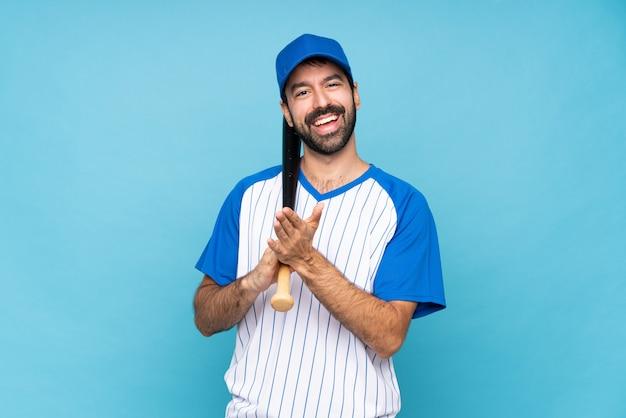 Jonge man spelen honkbal over geïsoleerde blauwe muur applaudisseren na presentatie in een conferentie