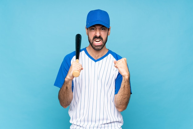 Jonge man spelen honkbal over geïsoleerde blauwe muur gefrustreerd door een slechte situatie