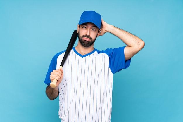 Jonge man spelen honkbal over geïsoleerde blauwe muur met een uitdrukking van frustratie en niet begripvol