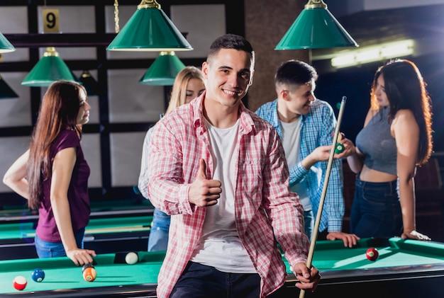 Jonge man spelen in biljart. poseren bij de tafel met een keu in zijn handen