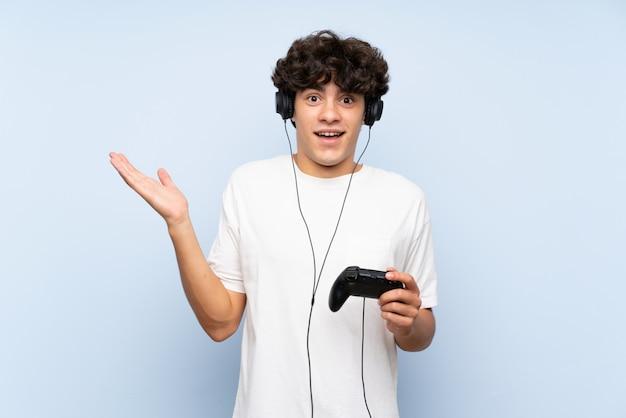 Jonge man spelen met een video game controller over geïsoleerde blauwe muur met geschokte gelaatsuitdrukking