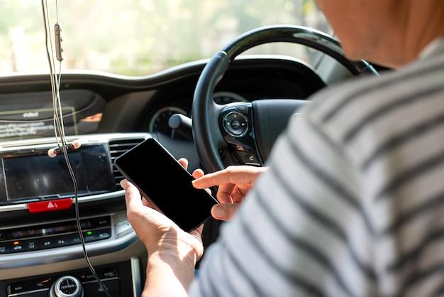 Jonge man spelen mobiel tijdens het besturen van de auto