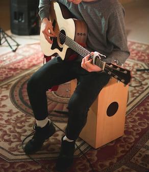 Jonge man spelen op akoestische gitaar