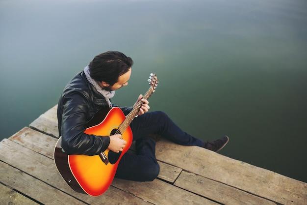 Jonge man spelen op gitaar op het meer