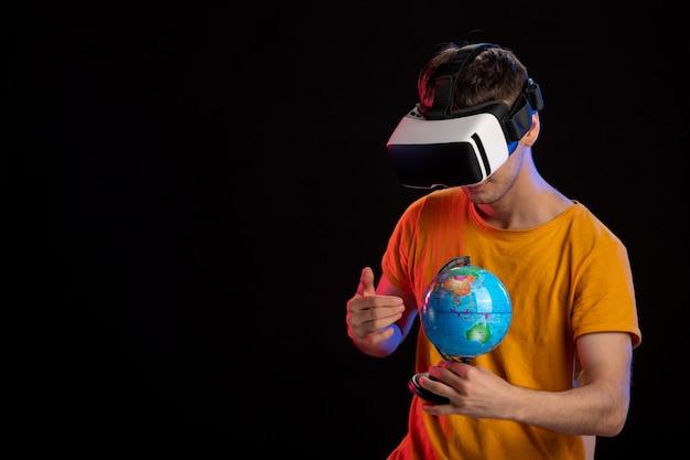 Jonge man spelen virtual reality globe houden op donkere ondergrond