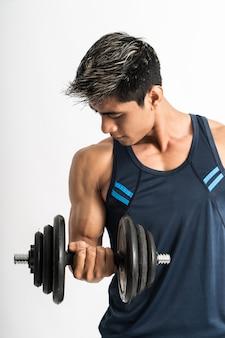 Jonge man spieren heffen haltergewichten met energie in de biceps