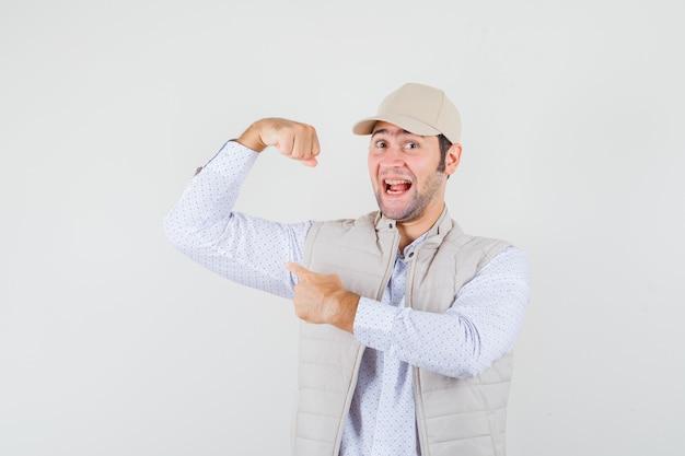 Jonge man spieren tonen en ernaar wijzen in beige jas en pet en op zoek gelukkig, vooraanzicht.