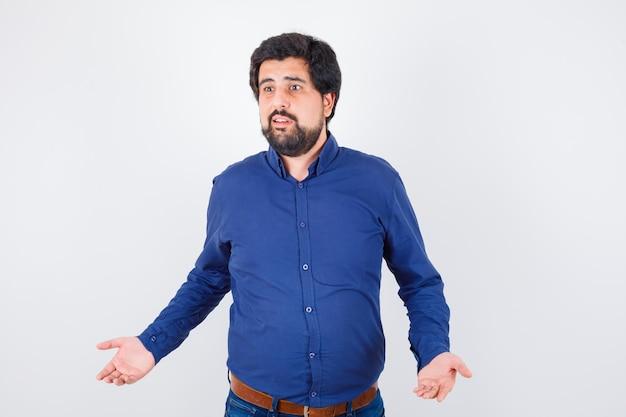 Jonge man spreidt de handpalmen opzij terwijl hij in een koningsblauw shirt spreekt en er spraakzaam uitziet, vooraanzicht.