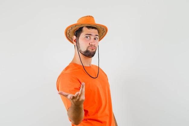 Jonge man spreidt hand op een verbaasde manier in oranje t-shirt, hoed vooraanzicht.