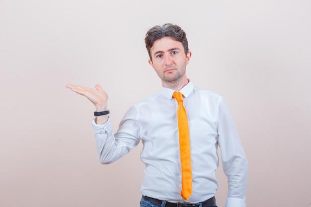 Jonge man spreidt palm opzij in shirt, spijkerbroek