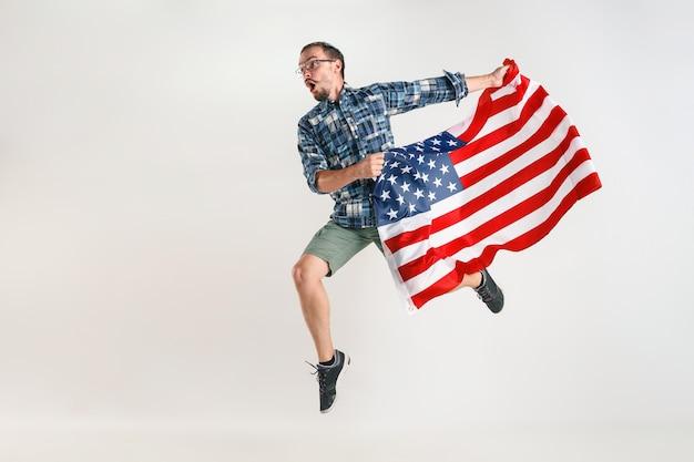 Jonge man springen met vlag van de verenigde staten van amerika geïsoleerd op witte studio.