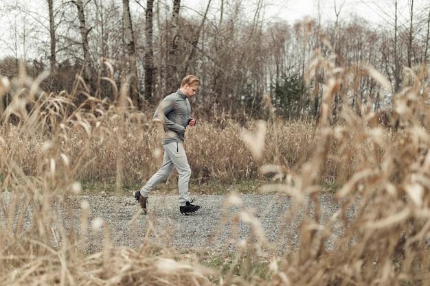 Jonge man springen over de plas op onverharde weg