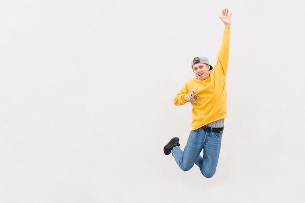 Jonge man springt met koptelefoon en muziek op een pastelblauw