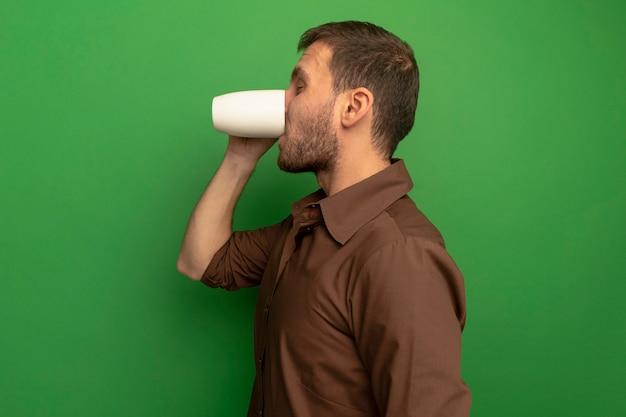 Jonge man staande in profiel bekijken kopje thee drinken met gesloten ogen geïsoleerd op groene muur