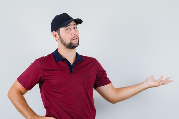 Jonge man staande met de hand op de taille terwijl hij opzij wijst in een rood t-shirt, zwarte pet en verbaasd kijkt. vooraanzicht.