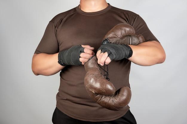 Jonge man staat en zet op zijn handen zeer oude vintage bruine bokshandschoenen