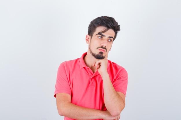 Jonge man staat in denkende pose in t-shirt en ziet er verstandig uit, vooraanzicht.