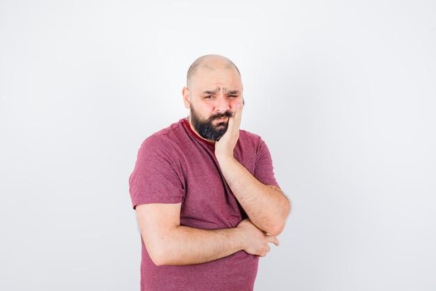 Jonge man staat in denkende pose, leunt op de handpalm in roze t-shirt en kijkt peinzend. vooraanzicht.