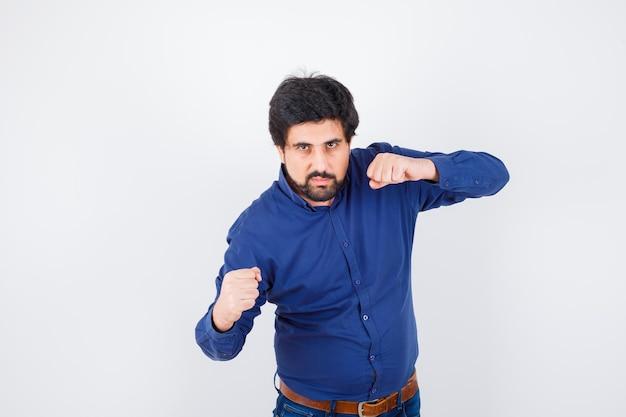 Jonge man staat in gevecht pose in shirt, spijkerbroek en ziet er hatelijk uit, vooraanzicht.