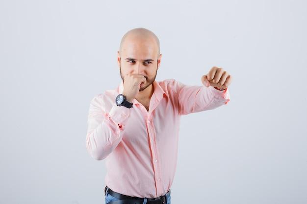 Jonge man staat in gevecht pose in shirt, spijkerbroek en ziet er zelfverzekerd uit, vooraanzicht.