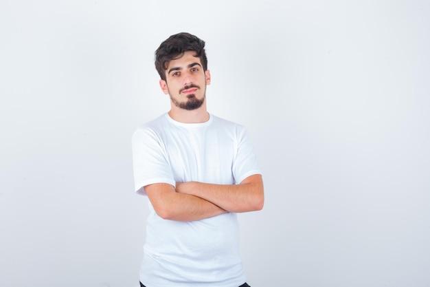 Jonge man staat met gekruiste armen in t-shirt en ziet er zelfverzekerd uit