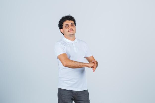 Jonge man staat met open handpalm en stopt gebalde vuist in wit t-shirt, broek en ziet er zelfverzekerd uit. vooraanzicht.