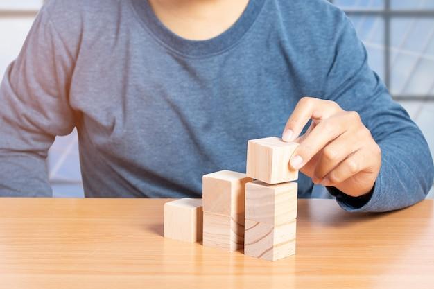 Jonge man stapelen houten blokken. leeg houtblok voor het invoegen van een zin, pictogram, symbool. bedrijfsontwikkelingsconcept.