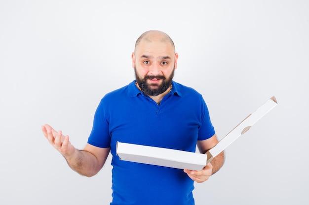 Jonge man steekt hand op in vragende pose terwijl hij pizzadoos in t-shirt vasthoudt en er gelukkig uitziet, vooraanzicht.